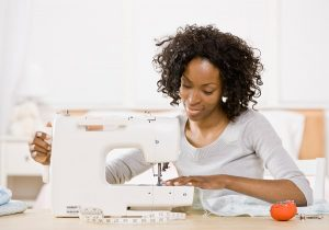 Creative woman using sewing machine to sew clothing